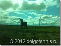 Бык  «Osborne» - один из символов Испании. Вдали ветряные электрогенераторы. Вид из окна автобуса.